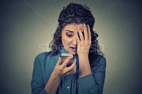 anxious scared young girl looking at phone seeing bad news photos message Stock photo © ichiosea