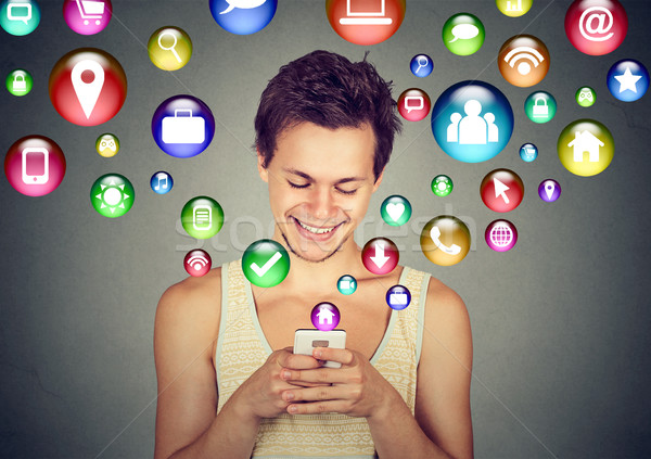 man using smartphone social media application icons flying up Stock photo © ichiosea