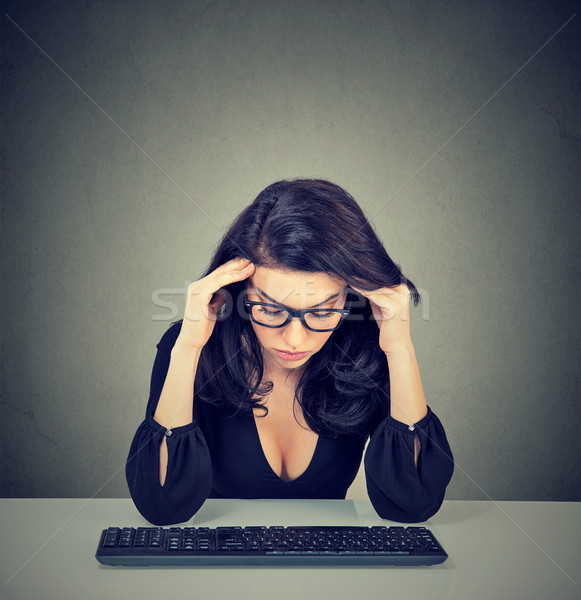 Stock photo: Overworked bored woman sitting at desk in front of her computer looking down