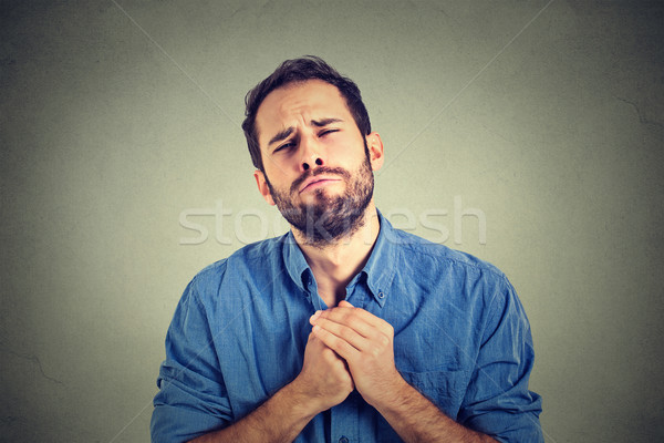 desperate young man showing clasped hands, pretty please asking help forgiveness  Stock photo © ichiosea
