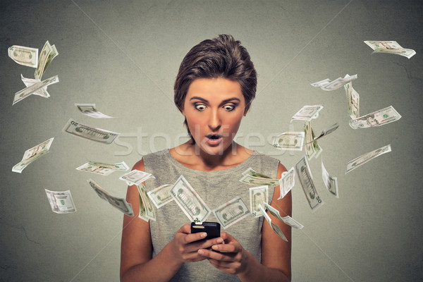 online banking concept. Shocked woman using smartphone dollar bills flying away Stock photo © ichiosea