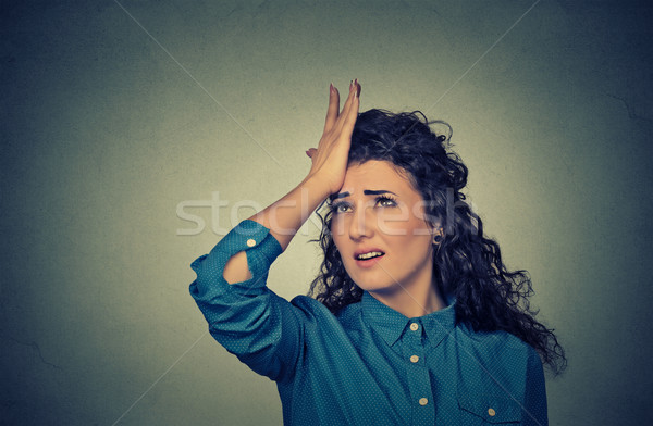 silly young woman, slapping hand on head having duh moment Stock photo © ichiosea