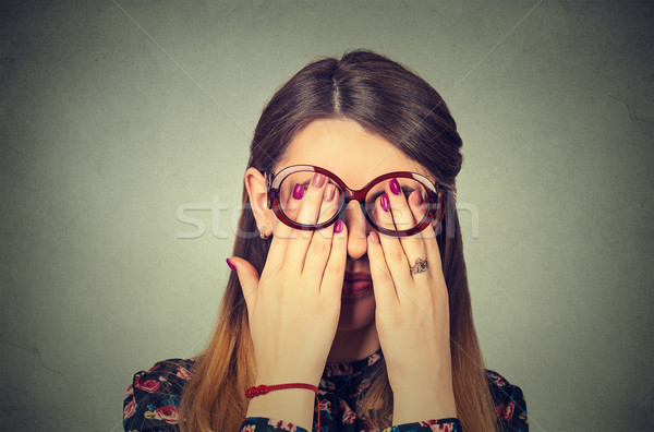 Closeup portrait young woman in glasses covering face eyes using her both hands  Stock photo © ichiosea
