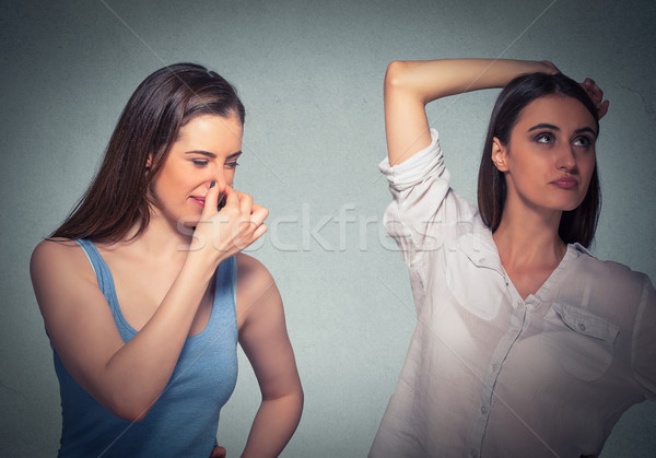 two women, one pinching nose something stinks, girls underarm  Stock photo © ichiosea