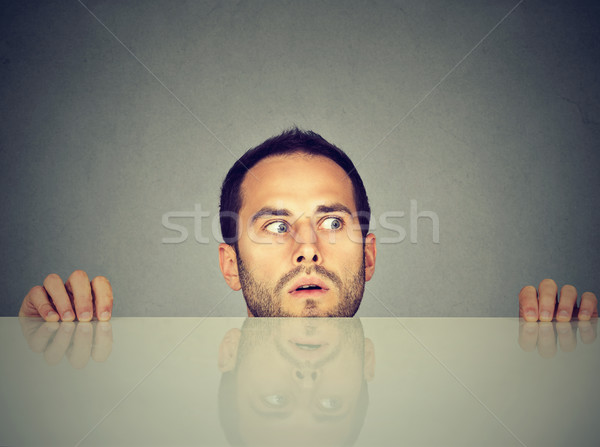 worried man looks at something peeking from under the table  Stock photo © ichiosea