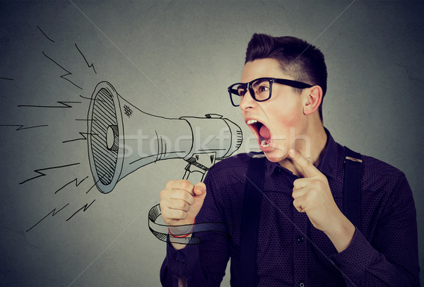 Angry young man screaming in megaphone  Stock photo © ichiosea
