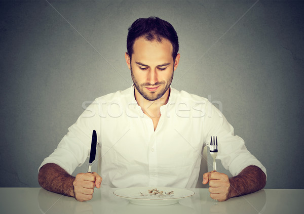 Man with fork and knife sitting at table looking at empty plate  Stock photo © ichiosea