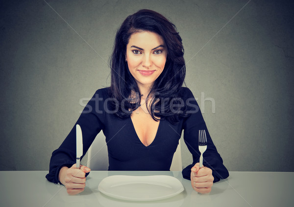 Happy woman with fork and knife sitting at table with empty plate  Stock photo © ichiosea