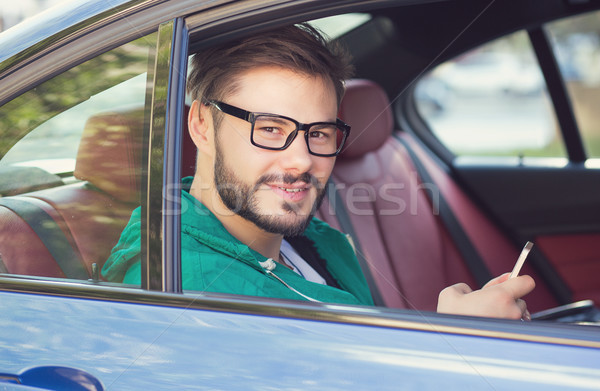 Casual hipster man in sitting in the car with smartphone looking at camera Stock photo © ichiosea