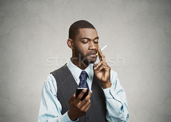 Executive man holding smart phone, smoking cigarette. Phone, nic Stock photo © ichiosea