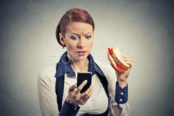 Business woman patrząc telefonu komórkowego jedzenie chleba kanapkę Zdjęcia stock © ichiosea