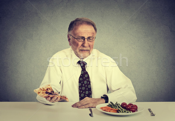 Senior man eating fresh vegetable salad avoiding fatty pizza. Healthy diet nutrition choices concept Stock photo © ichiosea