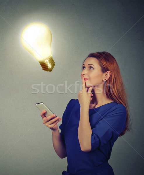Stock photo: Woman texting using mobile phone looking up at light bulb. Technology idea concept