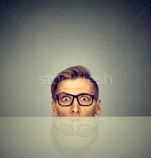 surprised businessman peeking from under the table  Stock photo © ichiosea