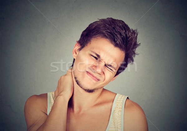 Stressed young handsome man with neck pain Stock photo © ichiosea