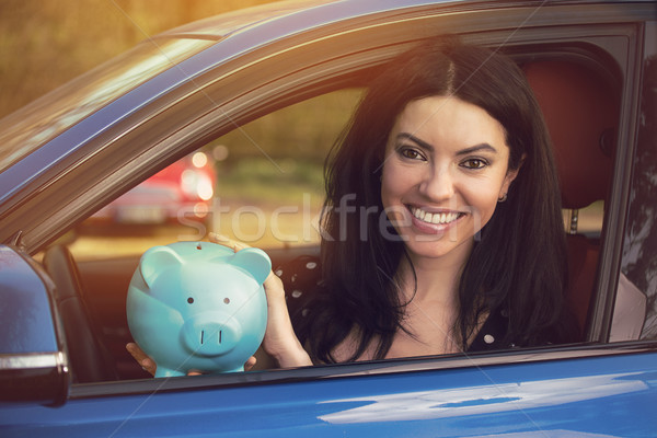 Happy woman sitting inside her car with piggy bank Stock photo © ichiosea