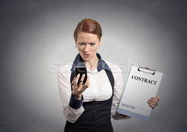 skeptical businesswoman holding contract looking on smartphone Stock photo © ichiosea
