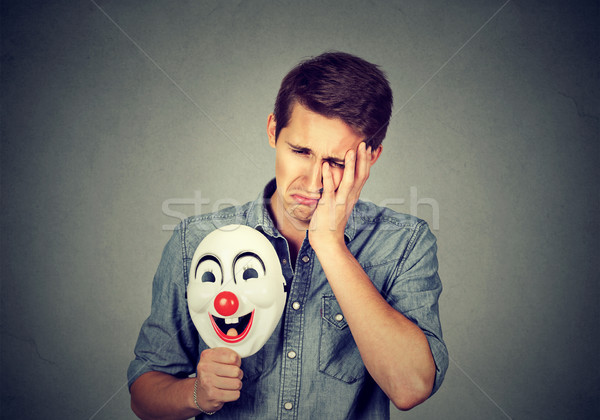 Young sad man with happy clown mask  Stock photo © ichiosea