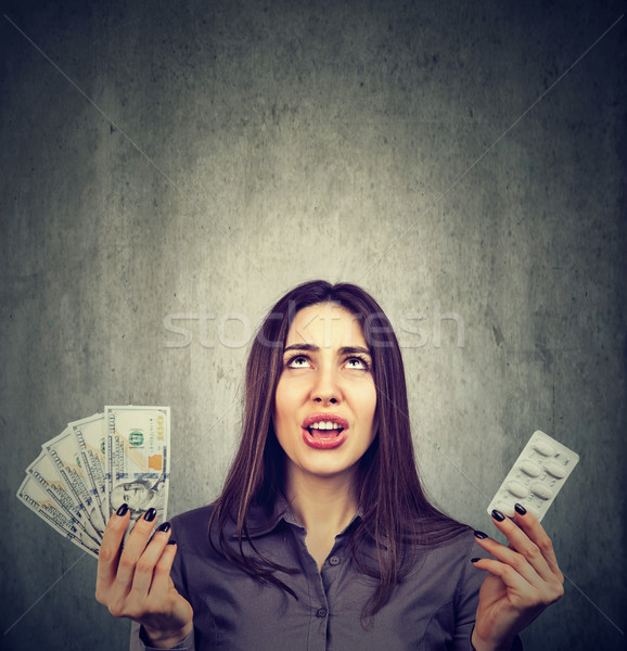 Healthcare costs. Upset woman with pills and dollar banknotes  Stock photo © ichiosea