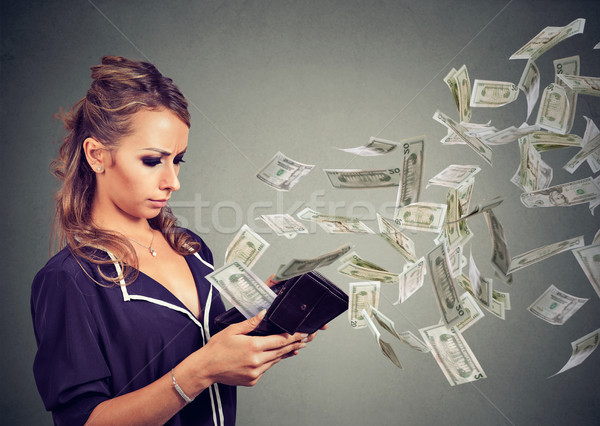 Sad young woman looking at her wallet with money dollar banknotes flying out away  Stock photo © ichiosea