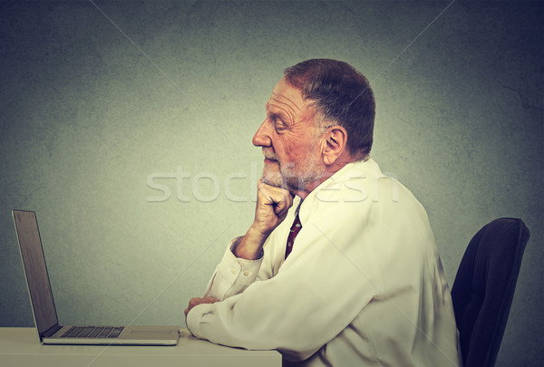 Senior man using laptop computer reading email news. E-learning concept  Stock photo © ichiosea