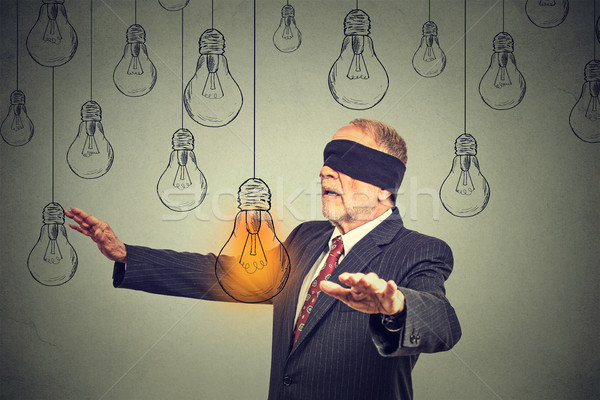 Blindfolded senior man walking through light bulbs searching for bright idea  Stock photo © ichiosea