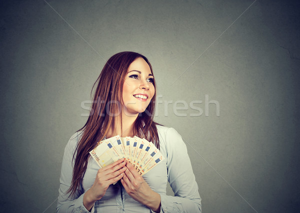 Woman holding money euro banknotes dreaming how to spend  Stock photo © ichiosea