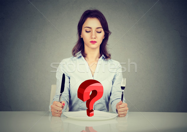 Young woman sitting at table with fork and knife looking at plate with red  question mark  Stock photo © ichiosea