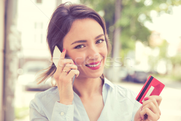 Happy woman buying online making an oder with a smart phone outdoors Stock photo © ichiosea