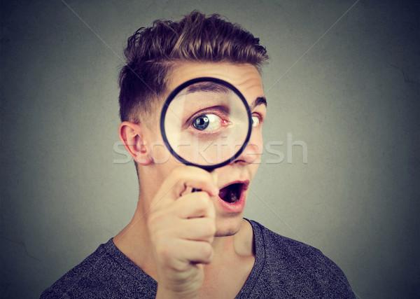 Singolare giovane guardando lente di ingrandimento uomo faccia Foto d'archivio © ichiosea