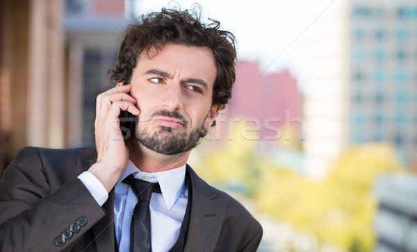 Portrait of a handsome serious businessman talking on a cell phone relaxed on a balcony of his apart Stock photo © ichiosea