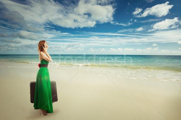 Stock fotó: Gyönyörű · nő · utazó · tengerpart · bőrönd · beszél · mobiltelefon