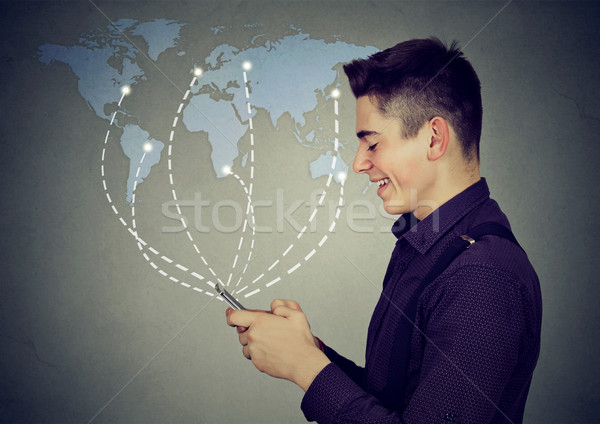 man using smartphone browsing internet on a worldwide map background Stock photo © ichiosea