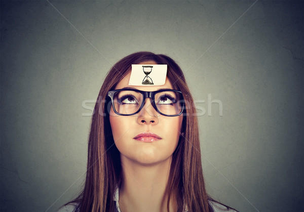 Thinking woman with sand clock sticker on forehead. Time management concept  Stock photo © ichiosea