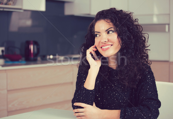 Stock photo: Pretty woman talking on mobile phone at home