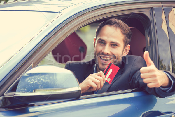 Happy man inside his new car showing credit card giving thumbs up Stock photo © ichiosea
