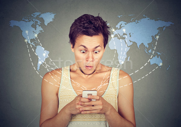 Shocked man looking at smart phone with world map on background  Stock photo © ichiosea