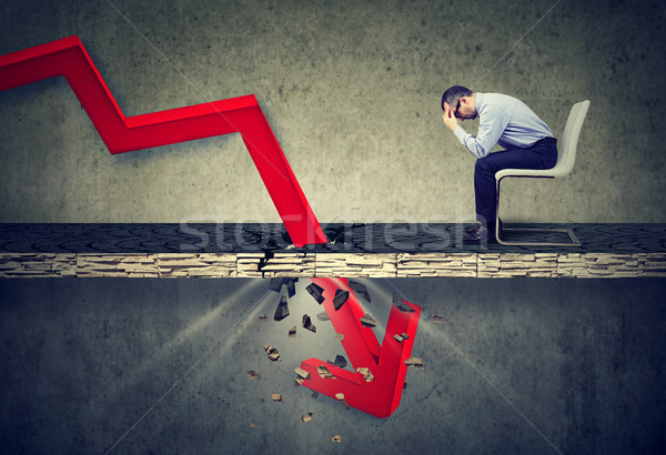 Depressed business man looking down at the falling red arrow going through a concrete floor.  Stock photo © ichiosea