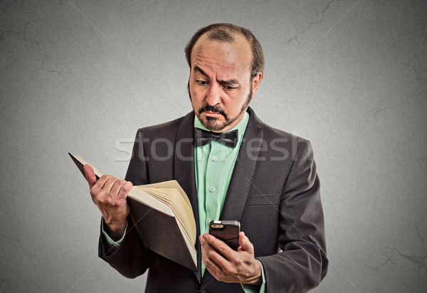 skeptical man reading news on smartphone, holding book Stock photo © ichiosea