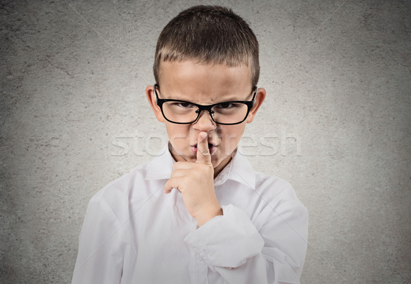Boy giving be quiet gesture with finger on lips Stock photo © ichiosea