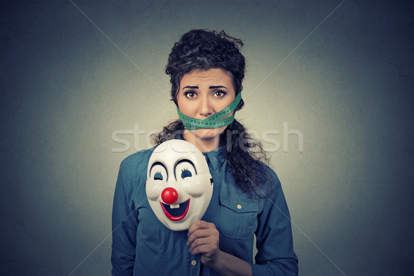 Diet restriction and stress concept. Portrait sad woman with clown mask and measuring tape around he Stock photo © ichiosea