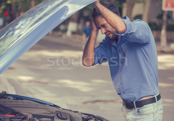 Stressed man with his broken car looking in frustration at failed engine Stock photo © ichiosea