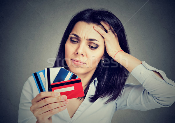 Stressed woman in debt holding at multiple credit cards Stock photo © ichiosea