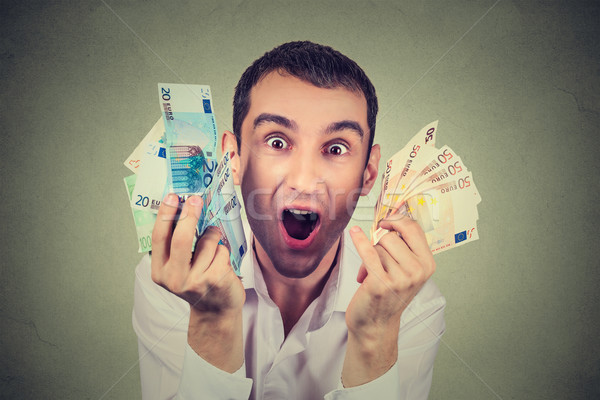 happy young man with money euro banknotes ecstatic celebrates success  Stock photo © ichiosea