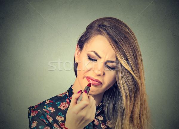 Annoyed displeased woman applying lipstick Stock photo © ichiosea