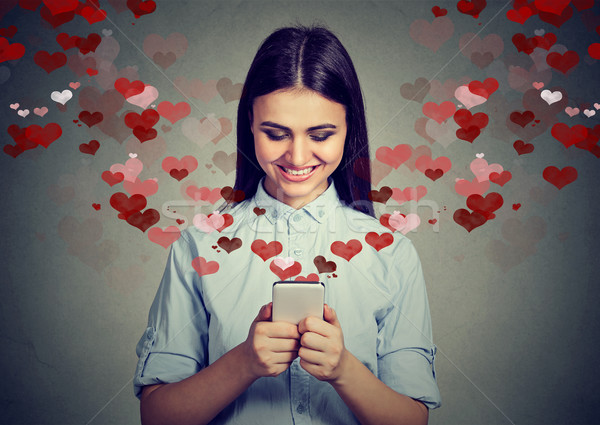 Happy woman sending love message on mobile phone hearts flying away  Stock photo © ichiosea