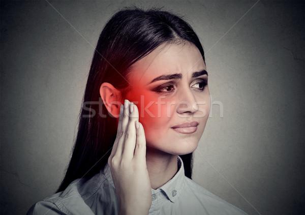 Tinnitus. Sick woman having ear pain touching her temple Stock photo © ichiosea