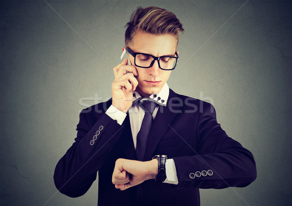 Stock photo: Businessman looking at wrist watch, talking on mobile phone.