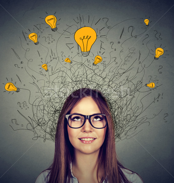 Woman in glasses with many ideas light bulbs above head looking up  Stock photo © ichiosea