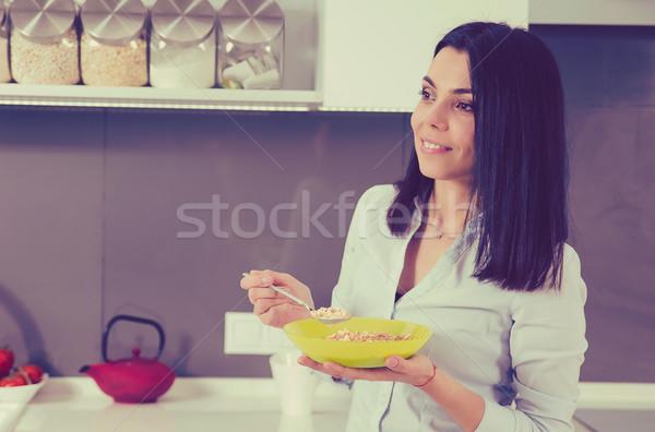 Beautiful young woman having breakfast in the kitchen. Stock photo © ichiosea